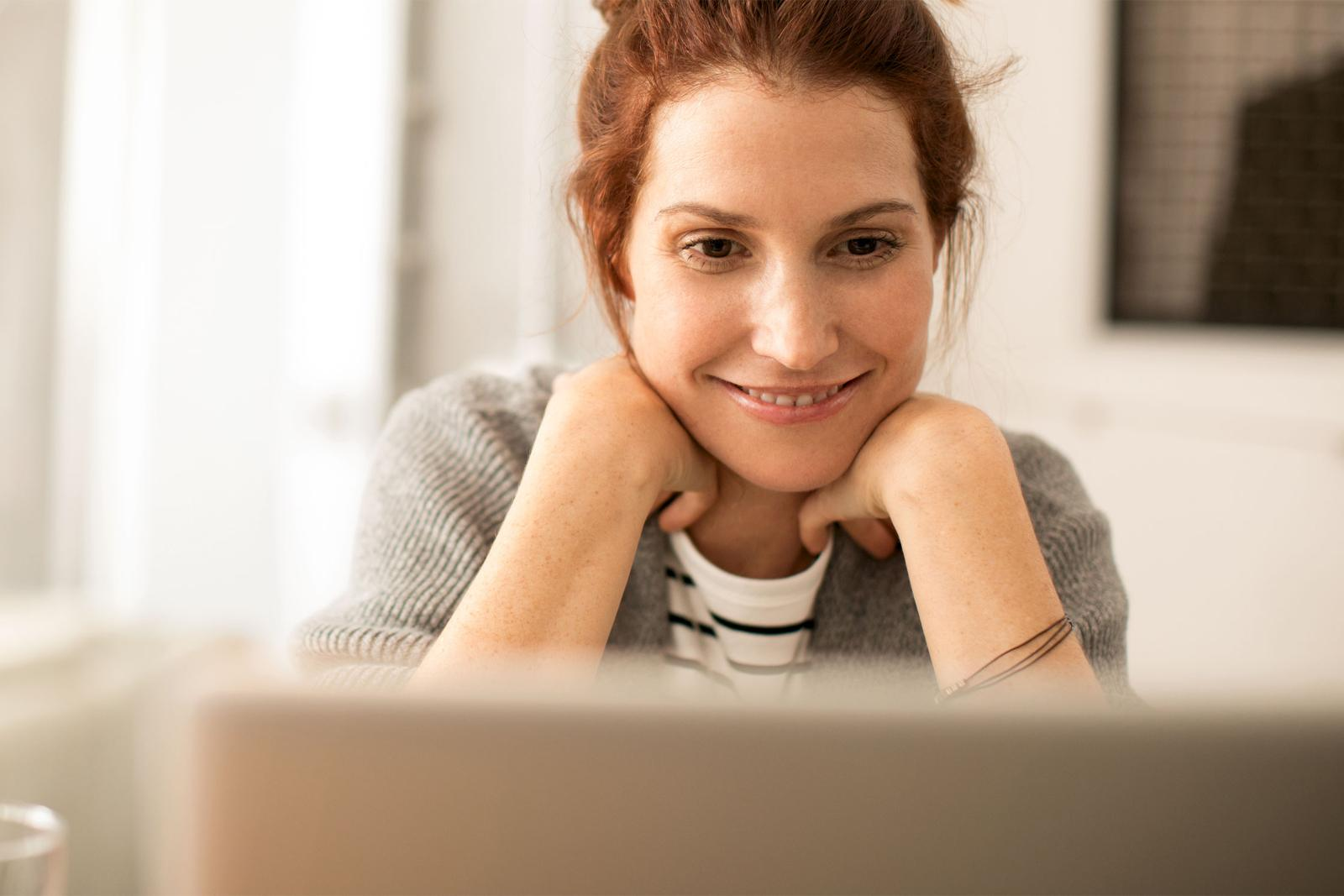young-woman-smiling-sitting-in-front-of-computer-pc-teaser.jpg